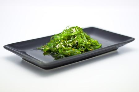 algas marinas: Copas de ensalada de algas saludable en plato negro con salsa de