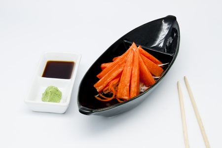 Crabsticks in black plate with sauce and vasabi Stock Photo