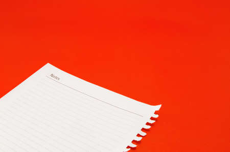 notebook paper on red background  photo