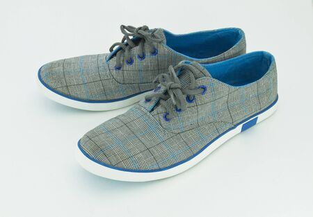 Blue sneakers over the white background