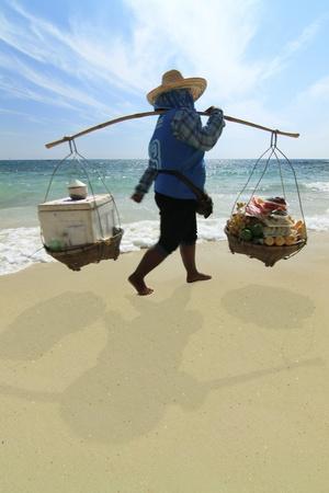 Thai traders walking along an off-season beach Stock Photo