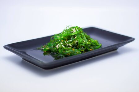 Seaweed Salad in black plate on white background