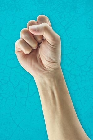 Hand with clenched a fist on background