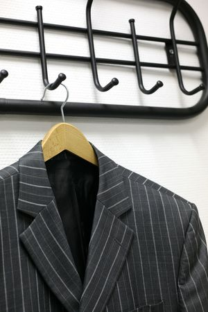 Mans jacket hanging on a coat hanger at a wall photo