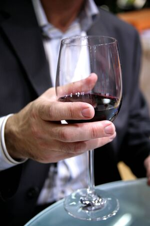 suggests: The man suggests to drink red wine Stock Photo