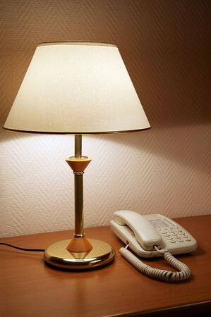 Phone on a table near to a lamp photo