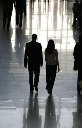 Silhouettes of people in a lobby of office building