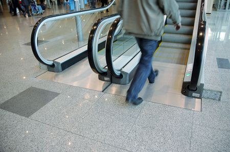 The person enters on the escalator at the airport photo