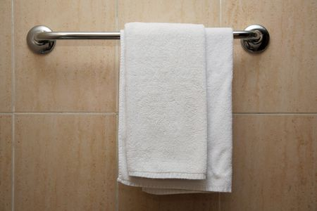 The towel hangs on a hanger in a bathroom