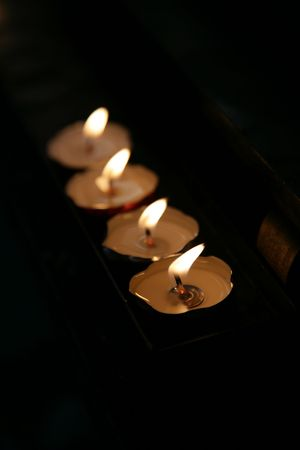 conflagrant: Four candle on support, conflagrant in darkness