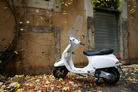 white scooter on parking near a house Stock Photo