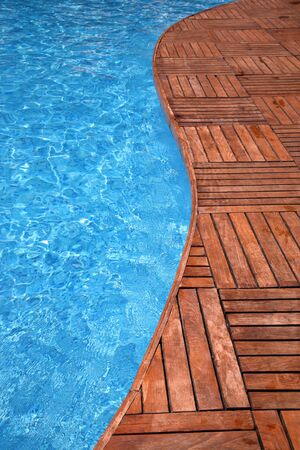 pool deck: Fragment of a swimming pool and wooden floor Stock Photo