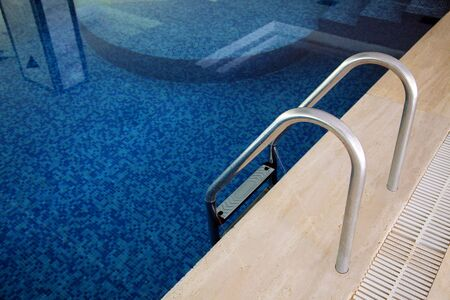 Fragment van zwembad met een ladder en doorzichtig water