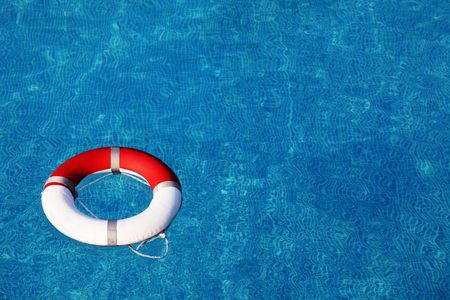 Red life buoy floating in swimming pool Stock Photo - 5533474