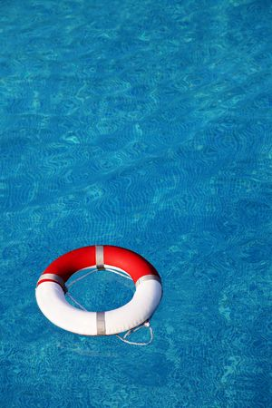 Red life buoy floating in swimming pool Stock Photo