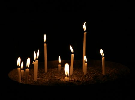 conflagrant: A few conflagrant candles are in darkness Stock Photo