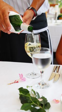 The waiter pours white wine in a glass photo