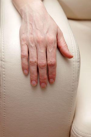armrest: Female hand on a sofa armrest Stock Photo