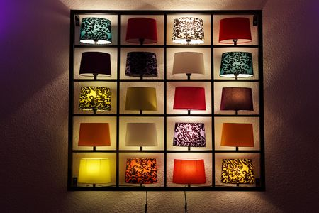 Various lamp on shelves near a wall photo