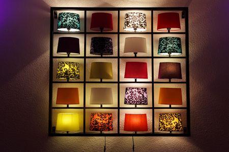 lamp shade: Various lamp on shelves near a wall