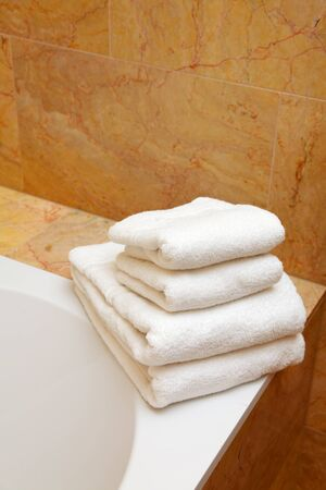 brink: Clean white towels on the brink of a bath