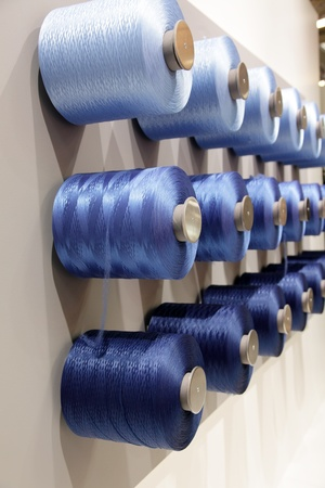 textile industry: spools with threads hanging on the wall