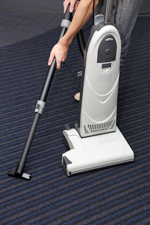man is cleaning the carpet vacuum cleaner photo