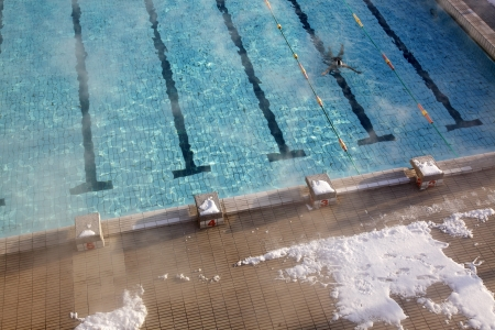 woman swims in the outdoor pool in winter photo