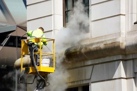een werknemer wast de gevel van het gebouw Stockfoto