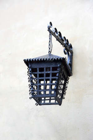 antique: old iron lantern on the wall of a building