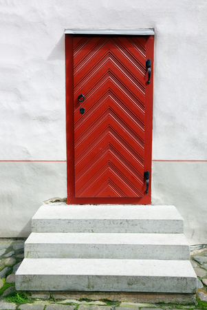building exteriors: Old door red, in the wall of the house Stock Photo