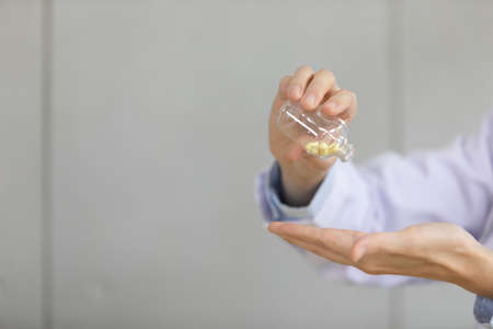 closeup doctor pouring capsule of vitamin or medicine from small glass bottle to his hand