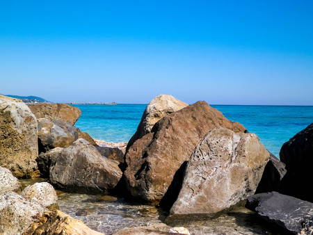 Stones on the beach in Vada, transparent, turquoise water and white sand. Travel and nature concept.