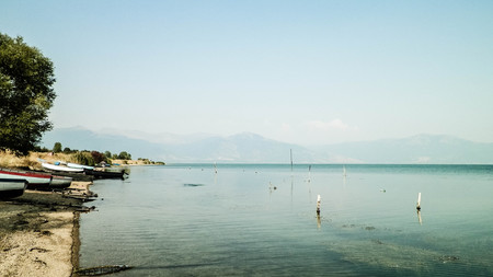 Fishing boats on coast of Lake Prespa and Mountains of Galicica National Park. Prespa lake is situated between Macedonia, Greece and Albania, known of it's wild nature and pelican reserve.