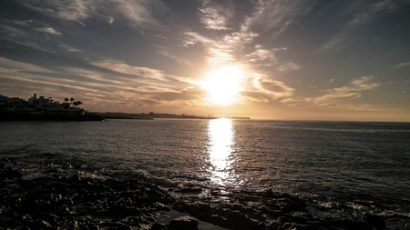 Beautiful nature background of sunset over beach in Playa Blanca, Lanzarote, Canarian Islands. Sunlight and Atlantic ocean. Vacations, tourism and nature concept. 免版税图像