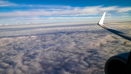 View of white clouds and plane enginie and wing. Transport concept. Copy space.
