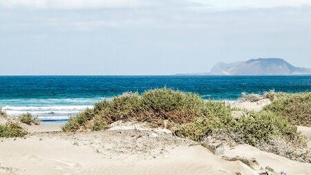 Beach, Atlantic Ocean and La Graciosa island in Caleta de Famara, Lanzarote Canary Islands. Beach in Caleta de Famara is very popular among surfers. Copy space. Stok Fotoğraf