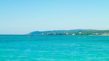 Coast in Italy in Vada, Tyrrhenian sea water on blue sky background. Vacations and nature concept. Copy space.