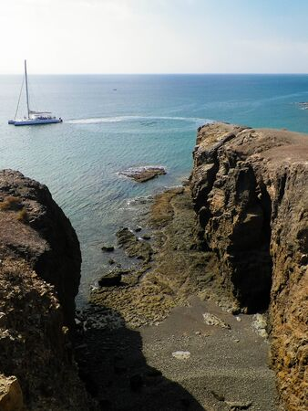 Sport, nature and leisure concept. Yacht boat close to coastal cliffs of Lanzarote island. Crystal clean Atlantic Ocean water.