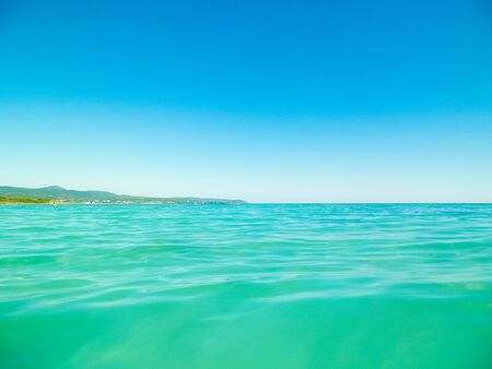Sea coast in Vada, Tuscany, Italy. Mediterranean nature in summer day, blue, Tyrrhenian sea water on blue sky background. Vacations and nature concept. Copy space.