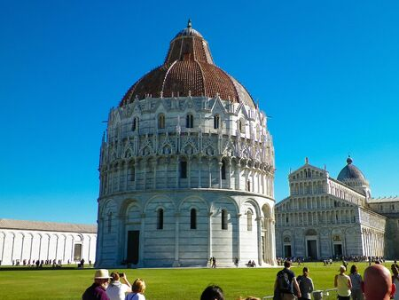 PISA, TUSCANY, ITALY, SEPTEMBER 21 2019: Piazza del Duomo in Pisa. Baptistery of St. John. Piazza del Duomo in Pisa is one of the worlds finest architectural complexes and important centre of European medieval art