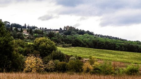 Autumn in Italy - Tuscan fields and hills on a cloudy day. Copy space on cloudy sky. Banco de Imagens
