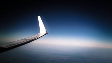 View from plane window on Planet Earth and plane wing. Travel and transport concept.