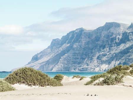 Beach and Mountains - beautiful coast in Caleta de Famara, Lanzarote Canary Islands. Beach in Caleta de Famara is very popular among surfers.