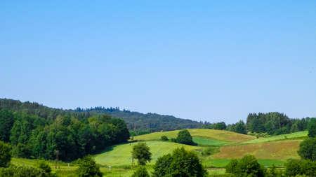 Hills, fields and meadows - beautiful landscape of Wiezyca, Kashubia Region, northern Poland. Copy Space on blue sky. 版權商用圖片 - 153404976