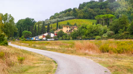 Road through a Tuscan Village. Autumn in Italy - Tuscan fields and hills on a cloudy day.