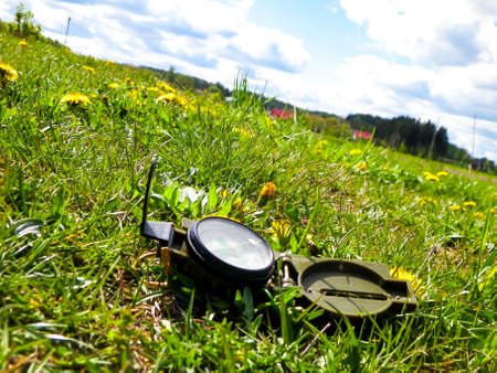 Compass on grass - traveling, exploration and navigation concept.