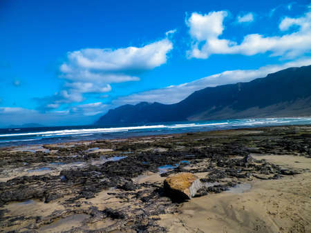 Beautiful coast in Caleta de Famara, Lanzarote Canary Islands. Beach in Caleta de Famara is very popular among surfers.