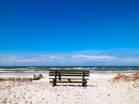 Bench on beach in Stilo, Baltic Sea coast, Poland. Copy space on blue sky.