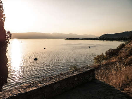 Coastal area of Ochrid Lake, Macedonia. View from park on sunset over Ochrid Lake. Ochrid is the oldest lake in Europe. Travel and nature concept.